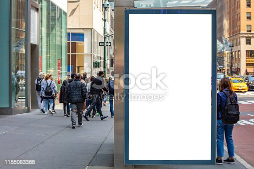 1036904778 istock photo Blank billboard at bus stop for advertising, New York city buildings and street background 1155063388