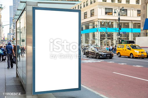 1036904778 istock photo Blank billboard at bus stop for advertising, New York city buildings and street background 1155063414