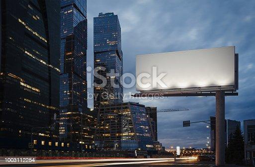 istock Blank billboard at twilight next to skyscrapers. 3d rendering 1003112254