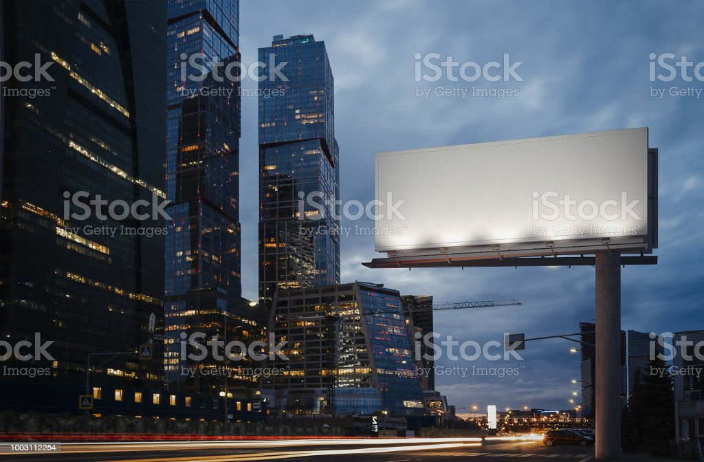 Blank billboard at twilight next to skyscrapers. 3d rendering stock photo