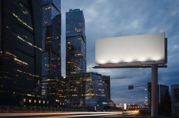Blank billboard at twilight next to skyscrapers. 3d rendering Blank billboard at night time in the city next to skyscrapers and road with lights on the frame. 3d rendering billboard stock pictures, royalty-free photos & images