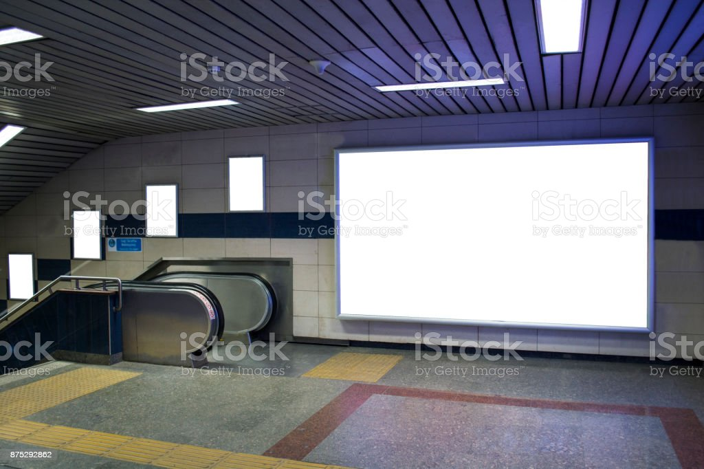 blank billboard beside escalator in subway useful for your advertising stock photo