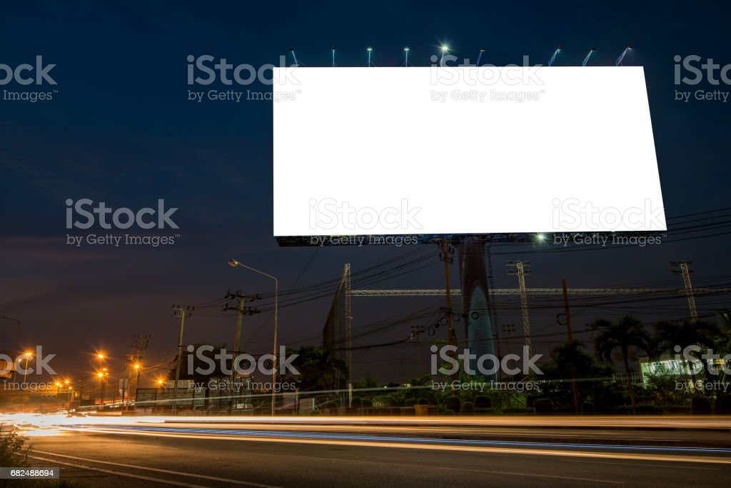 Blank billboard for advertisement at twilight time with light trails on the road at dusk Стоковые фото Стоковая фотография