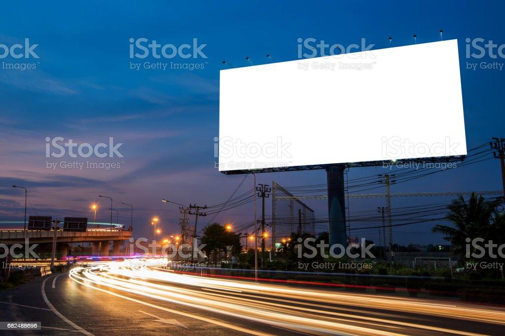 Cartelera en blanco para la publicidad en tiempo de Crepúsculo con senderos de luz en el camino al atardecer foto de stock libre de derechos
