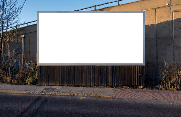 Blank billboard for customisation in an urban location Billboard blank near road and pavement for customisation. Outdoor landscape rectangular advertising display for insertion of creative designed content billboard stock pictures, royalty-free photos & images