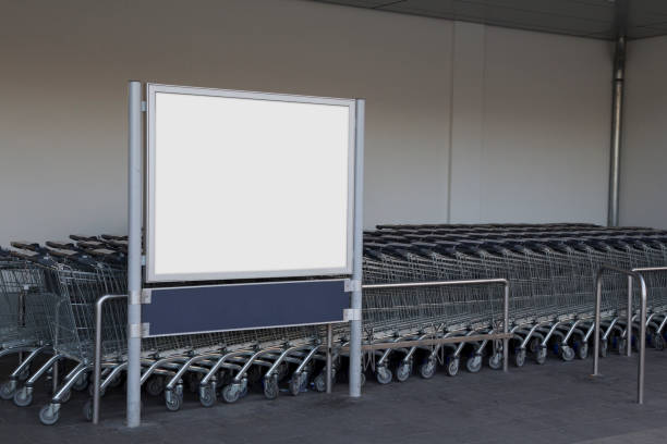 Blank billboard in a supermarket Blank billboard in a supermarket, next to shopping carts discount store stock pictures, royalty-free photos & images