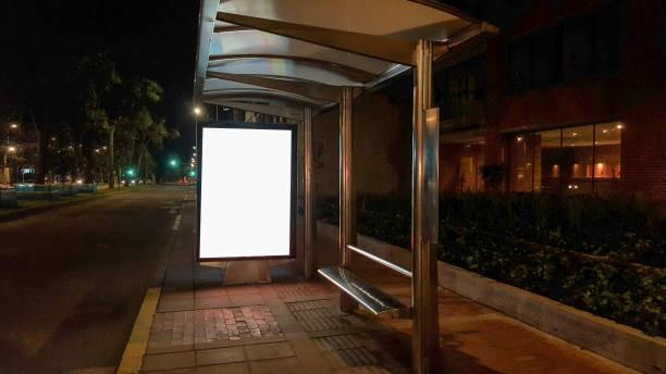 lege billboard in bus stop 's nachts - bushalte stockfoto's en -beelden