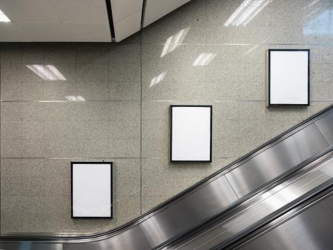 Blank billboard in subway station with escalator.