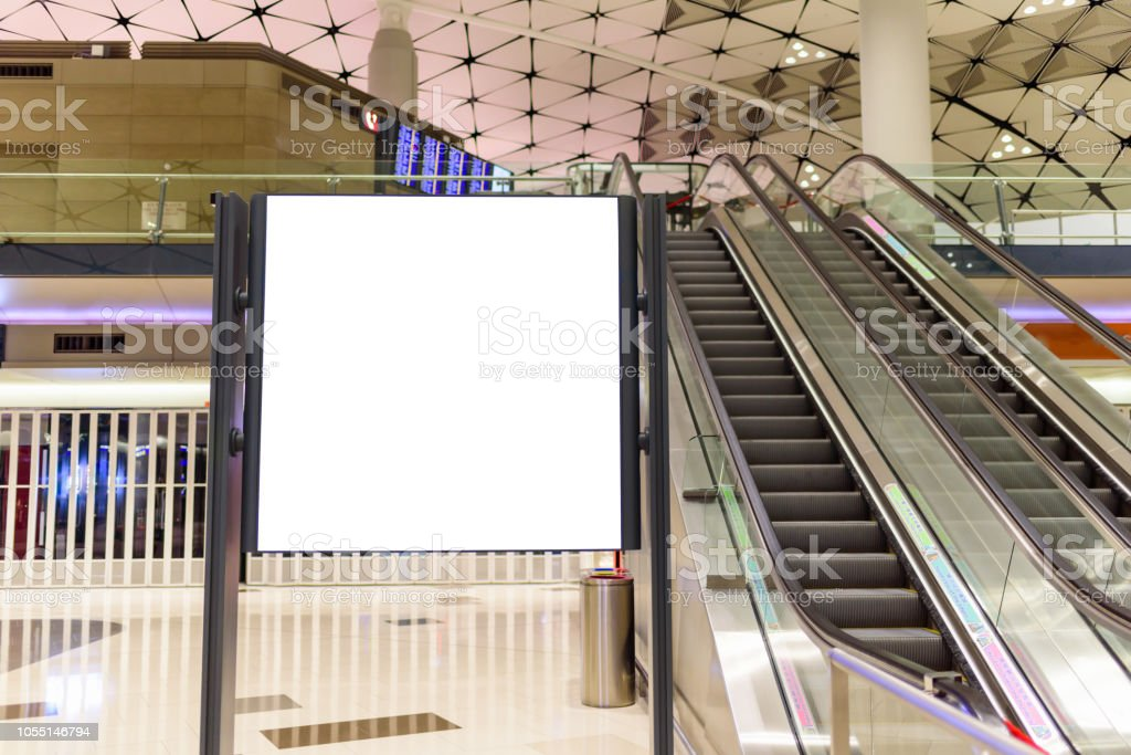 Blank billboard  located near escalator in shopping center or airport terminal stock photo