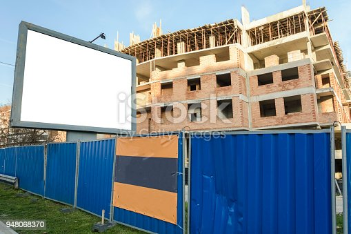 istock Blank billboard near a building in construction. 948068370