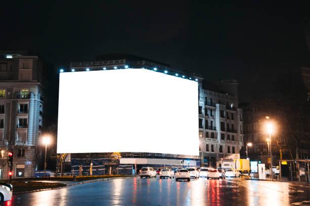 leere billboard auf gebäude in der nacht - plakatieren stock-fotos und bilder