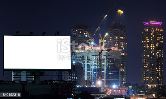 istock Blank billboard on construction crane and building in the night 640192316