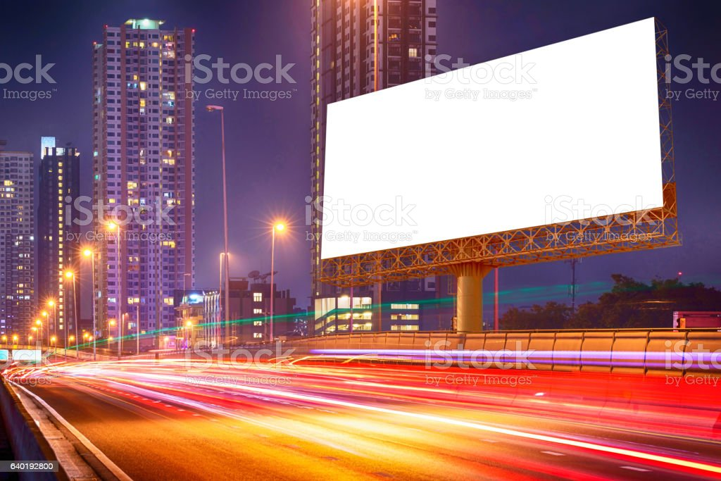 blank billboard on light trails, night street and urban stock photo