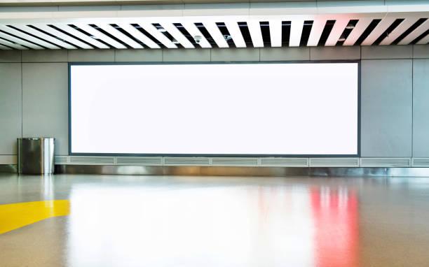 leere plakatwand auf dem flur des flughafens - plakatieren stock-fotos und bilder