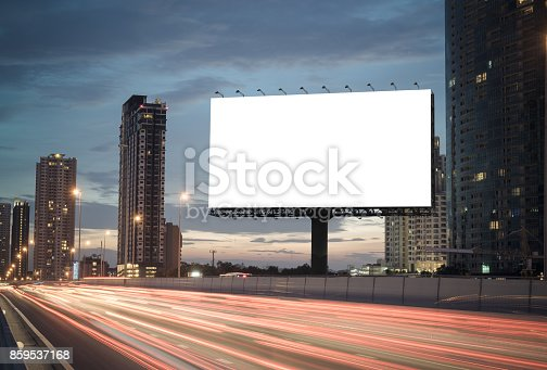 Blank billboard on the highway during the twilight with city background with clipping path on screen.- can be used for display your products or promotional