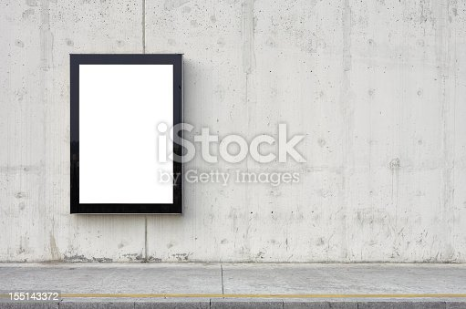 Blank billboard on wall. Wall is made of concrete and gray coloured. Billboard is oriented vertically and standing on the left side of frame. Edges of billboard are black. Billboard is empty so you can write or add something on it. - Clipping path of billboard included.