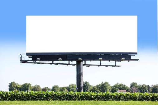 Blank billboard standing in a soybean field along a road.