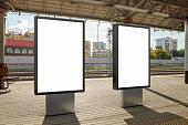Two blank billboard poster stands mock up on platform of railway station. 3d illustration.