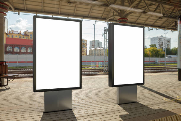 Blank billboard poster stand mock up on platform of raillway station Two blank billboard poster stands mock up on platform of railway station. 3d illustration. railroad station stock pictures, royalty-free photos & images