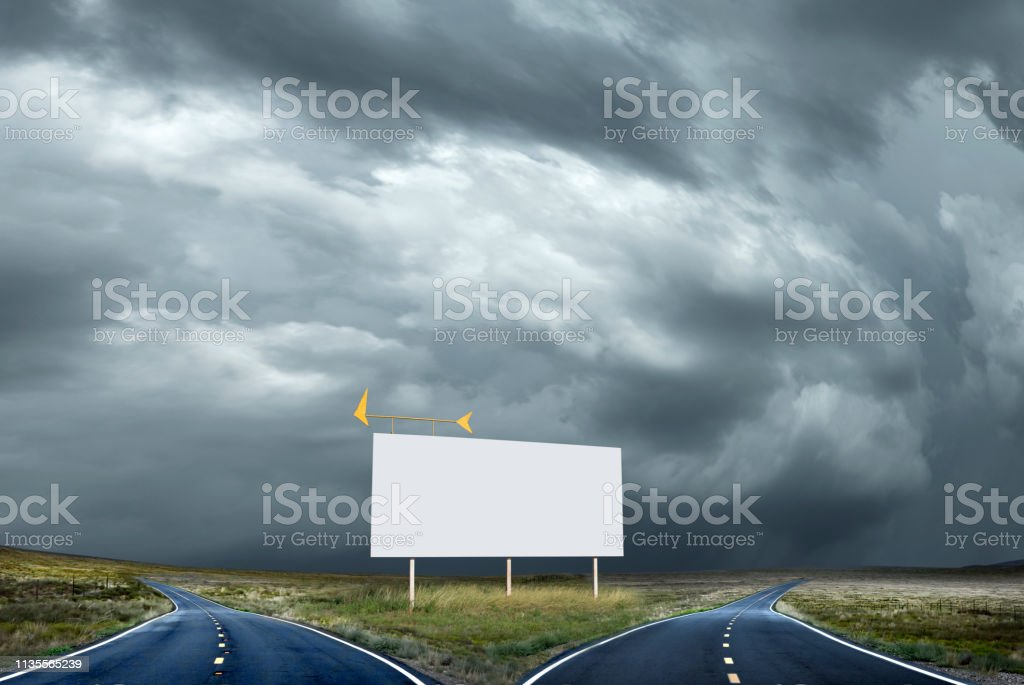 Blank Billboard Stands At A Fork In The Road Against Stormy Skies stock photo