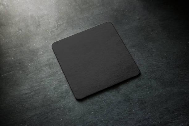 leere schwarzbier achterbahn modell auf grauen schreibtisch liegen - untersetzer stock-fotos und bilder