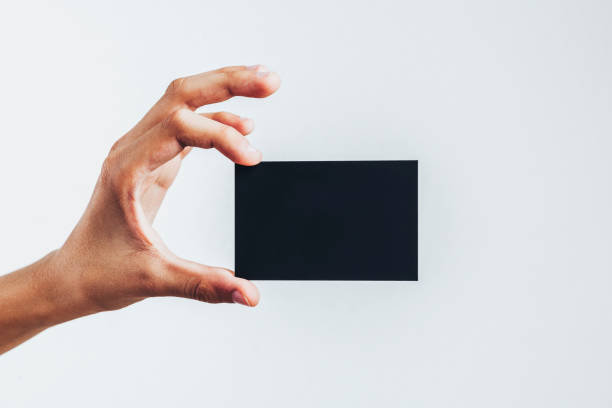 blank black card in a hand - gift voucher or card stock photos and pictures