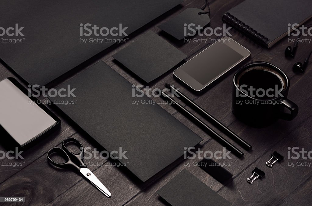 Blank black corporate stationery with phone on dark stylish wood background, inclined, closeup. stock photo