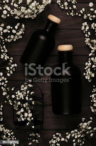 847096968 istock photo Blank black cosmetics bottles with white small flowers on dark wood board, mock up, top view. 864366840