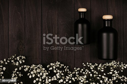 847096968 istock photo Blank black cosmetics bottles with white small flowers on dark wood board, mock up, top view, copy space. 864404656