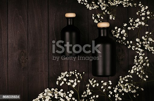 847096968 istock photo Blank black cosmetics bottles with white small flowers on dark wood board, mock up, top view, copy space. 868005634