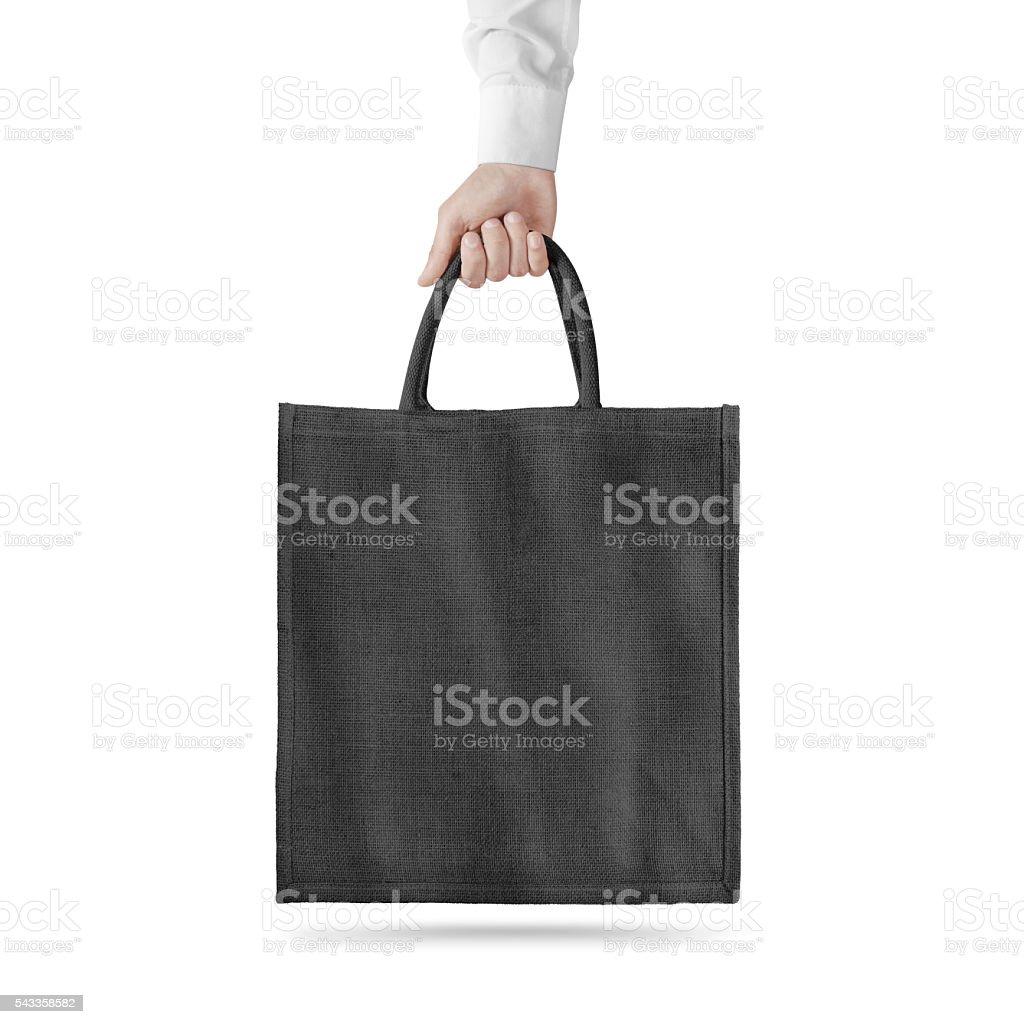 Blank black cotton eco bag design mockup isolated, holding hand stock photo