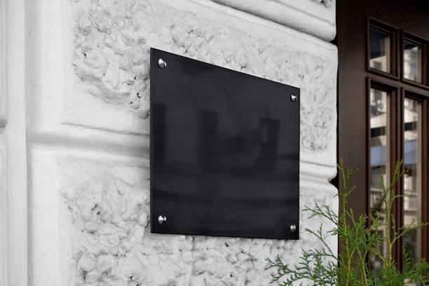 Blank black glass signplate on textured wall mockup stock photo