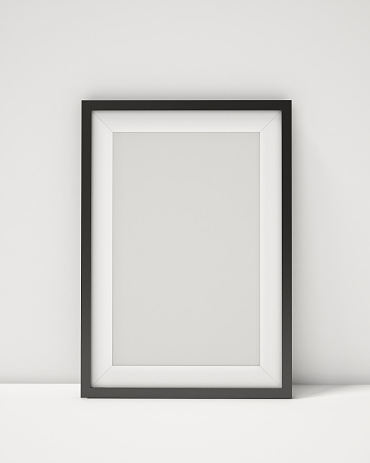 blank black picture frame on the white interior background