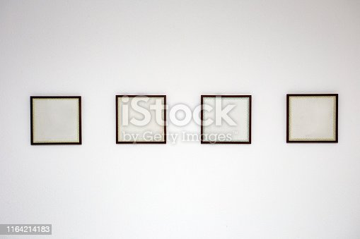 istock Blank black picture frame template for place image or text inside on the white wall in a row 1164214183