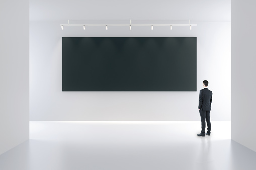 Blank black poster and businessman in white empty room, mock up