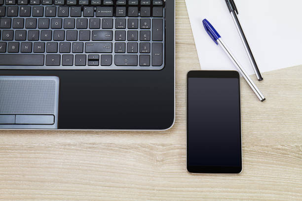 Blank black screen smartphone beside laptop with paper and pens on wooden desk, business concept Blank black screen smartphone beside laptop with paper and pens on wooden desk, business concept alongside stock pictures, royalty-free photos & images