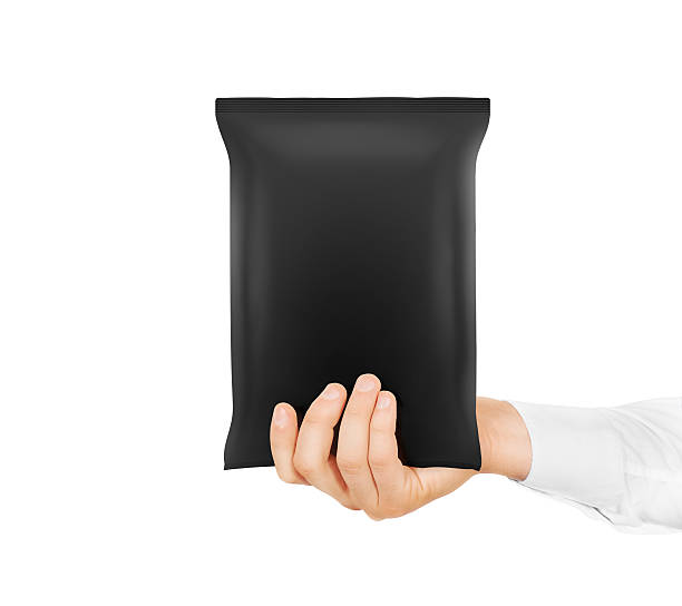 blank black snack bag mock up hold in hand isolated. - crisp packet stock photos and pictures