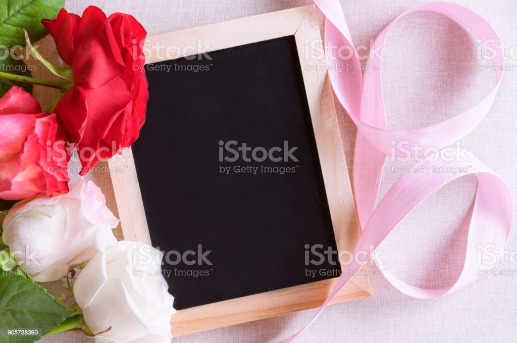 Blank blackboard and roses with ribbon stock photo