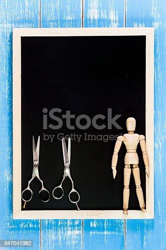istock Blank blackboard and scissors hairdresser on wooden table. 547041362