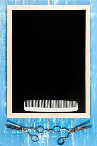 istock Blank blackboard and scissors hairdresser on wooden table. 547041510