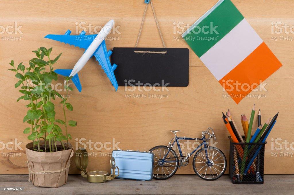Tableau noir blanc, drapeau de l'Irlande, modèle d'avion, petit vélo, valise, Compas, crayons - Photo