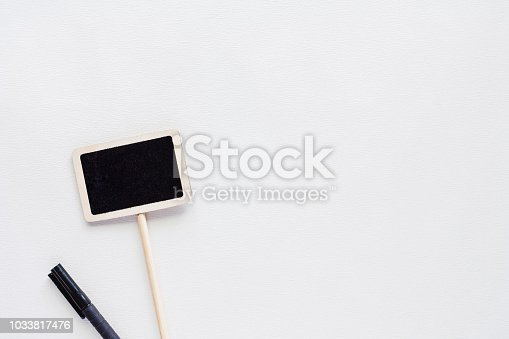 923869178 istock photo Blank blackboard label stick with pen on white background for writing information on it 1033817476