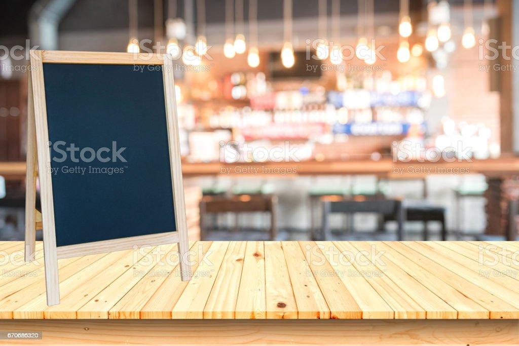 Leere Tafel Zeichen und Holztisch mit unscharfen Café Hintergrund. – Foto