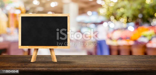 istock Blank blackborad on wooden table top with blur people shopping at supermarket bokeh background,Mock up for display or montage of design. 1159345548