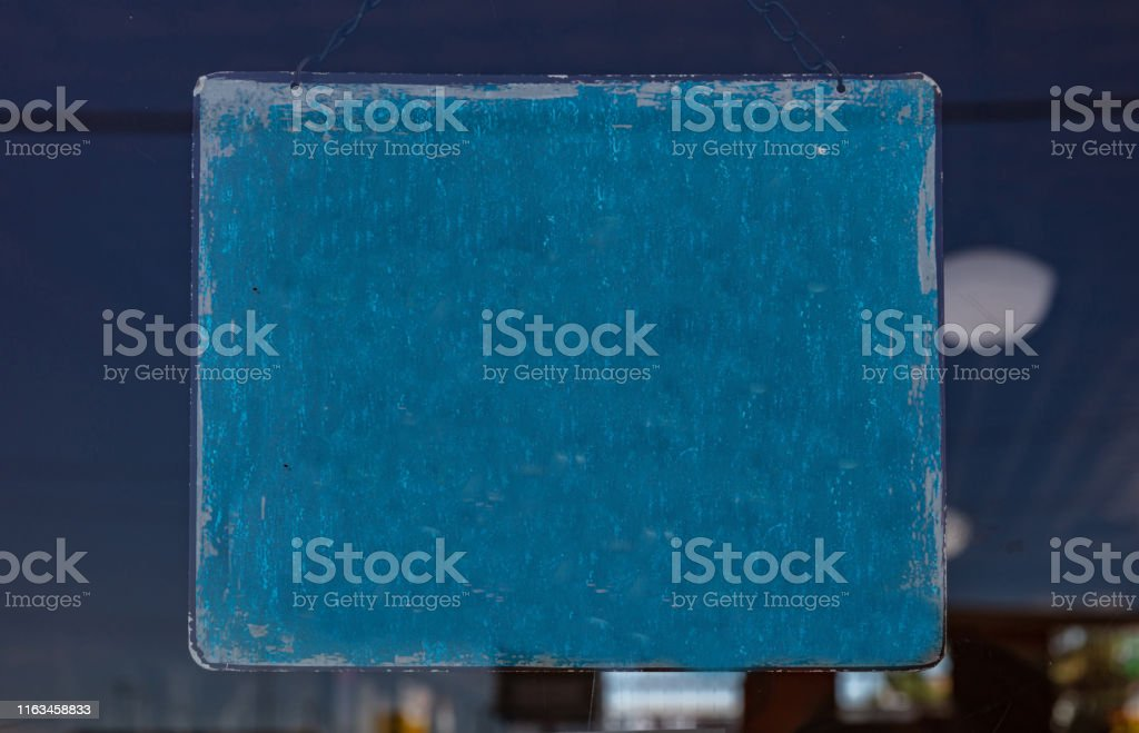 Shop blank sign. Blank sign, blue color, faded and old hanging on a...