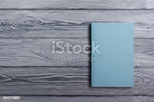 istock Blank book cover on textured wood background. Copy space 484373856