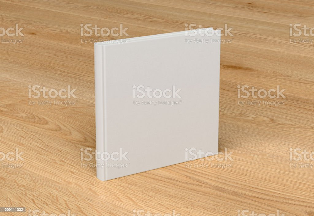 White blank square book cover standing isolated on glossy wooden...
