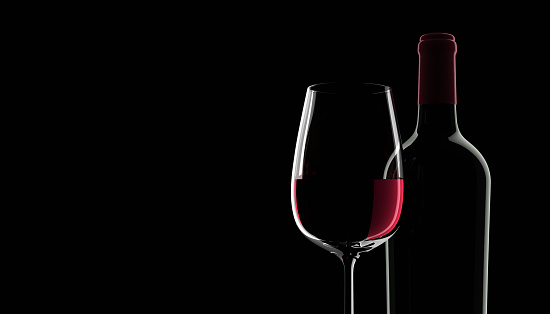 Blank bottle of red wine and glass with dark background