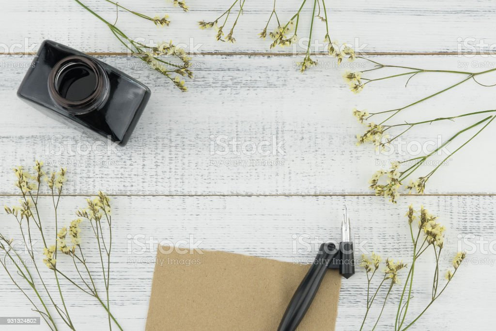 Blank brown card, oblique pen and bottle of ink decorated with yellow limonium caspia flowers stock photo