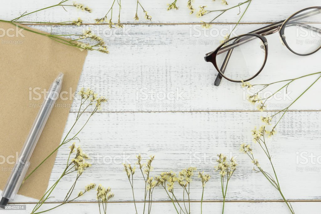 Blank brown card, pen and eyeglasses decorated with yellow limonium caspia flower stock photo